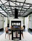 Rustikale Tafel aus dunklem Holz und Stühle im Retro-Stil auf Teppich in hallenartigem Wohnraum mit sichtbarer Dachkonstruktion; Raumteiler vor Loungebereich