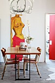 Dining table with metal frame and retro chairs below postmodern pendant lamp; painting on wall in background