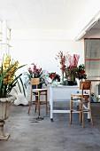 Arbeitstisch eines Floristen umgeben von verschiedenen Blumen in schlichtem Raum