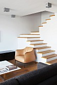 Staircase with wooden treads and no handrail in minimalist, open-plan living area of architect-designed house