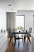 View from white fitted kitchen with wooden floor into open-plan dining area with dark, designer chairs