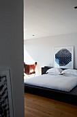 Schwarzes Doppelbett mit gerahmtem modernem Bild auf Bettkopfteil gestellet
