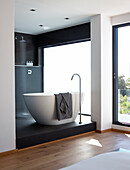 Purist ensuite bathroom with free-standing, white, designer bathtub and shower area on black platform