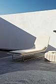 Elegant, white designer lounger on grey, stone flags of terrace against white wall of sunny courtyard
