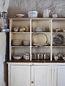 Schlichtes, weisses Küchenbuffet mit Geschirr in offenem Aufsatz vor rustikal verputzter Wand