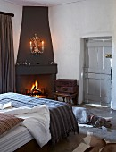 Bedroom with cosy open fire in corner fireplace - dog on floor at foot of bed