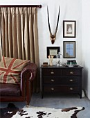 Hunting trophy on wall above dark wood chest of drawers next to leather sofa in front of window with floor-length curtains