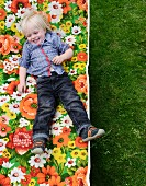 Little boy lying on floral garden lounger (top view)