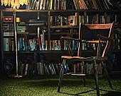 Alter Holzstuhl & Stehlampe vor Bücherregal