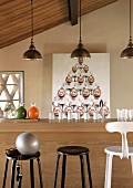Bar stools at counter with carafes of drink and glasses below group of pendant lamps; caricature on wall