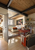 Open-plan living - armchair next to rustic table with bed on platform in background