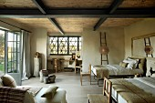 Twin double beds in simple room in country house with wood-beamed ceiling
