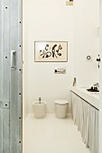 Loft bathroom with pale colour scheme, abstract painting above toilet and bidet next to washstand counter with curtain on base unit and steel sliding door in foreground