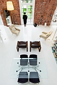 View from gallery down into loft apartment with brick walls, black chairs at large glass table and armchairs arranged casually on purist white floor