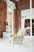 Retrosessel unter Klassiker Bogenlampe von Achille Castiglioni in einem puristisch leeren Loftraum mit Backsteinwand und weiss lackiertem Boden