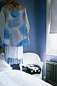 Hängende Kleidung und lackierter Stuhl im Schlafzimmer