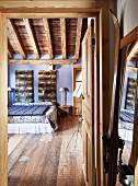 Blick durch offene Tür in rustikales Schlafzimmer mit Dielenboden