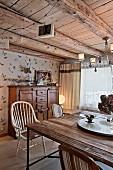 Tisch mit rustikaler Holzplatte und Vintage-Stühlen in Wohnzimmer mit Holzbalkendecke