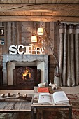 Wooden table in front of fire in open fireplace and decorative letters on mantelpiece in wooden chalet