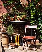 Klappstuhl, Stiefel, Blumenkübel & Wandkonsole mit Blumentöpfen vor Hauswand im Garten