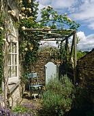 Klappstuhl auf kleiner Terrasse unter rosenberankter Pergola eines Landhauses