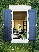 Blick von Aussen durch ein Fenster in begrünter Hausfassade mit blauen Fensterläden in den Wohnraum