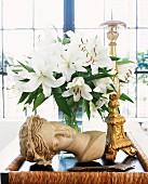 Interior Stillleben mit Büste und weiße Lilien neben goldenem Kerzenständer auf Tablett