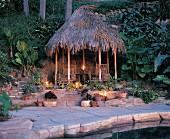Tiki Hütte am Pool mit Kerzen in tropischen Garten bei Abenddämmerung