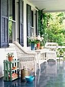 weiße Korbmöbel auf der Veranda vor Hauswand mit blauen Fensterläden
