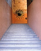 Stone stairs rise towards a sun sculpture in Italy
