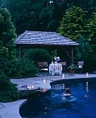 Frau im Pool in der Abenddämmerung mit Kerzen am Beckenrand und Sitzplatz vor Unterstand