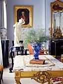 Wohnzimmer mit blauer Kristallvase auf Tisch mit vergoldeten Schnitzereien und Antiquitäten im Hintergrund