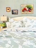 Doppelbett mit Kopfteil und Bettwäsche mit floralem Muster in Weiss und Hellgrau