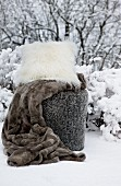 Fur blanket and flokati cushion in snow