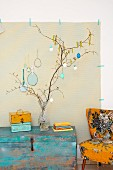 Branches hung with painted Easter eggs in glass vase on vintage wooden trunk next to armchair with 50s-style patterned upholstery