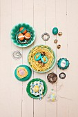 Various Easter eggs on nests of straw, bent wire and ribbon in bowls on pale wooden surface