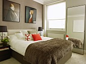 Two portraits above bed with upholstered frame and full-length mirror leaning against wall in classic bedroom
