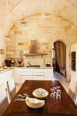 Modern, L-shaped kitchen counter, large oak table, traditional stone walls and vaulted ceiling