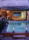 Romantische Dämmerstimmung mit Windlichtern an Pool-Umrandung; Sitzplatz vor rustikalem Landhaus im Hintergrund