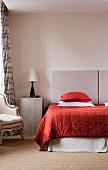 Naturtöne mit kräftigem Rot im Schlafzimmer - Holzkiste als Vintage Nachttisch und modernes Doppelbett mit gesteppter Tagesdecke