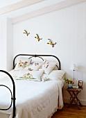 Bunte Vogelfiguren an der Wand über romantischem Metallbett im Landhausstil