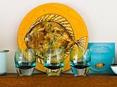 Drei blau schimmernde Trinkgläser vor gelber Platte mit Fischmotiv und daneben eine Abbildung mit Fisch im Wasserglas