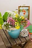 Improvisierter Nachttisch - Vase mit Wiesenblumen und Retro Wecker auf Holzklapptisch