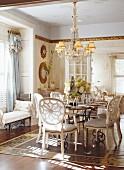Offener Wohn/Essraum im antikisierenden Stil mit festlich gedecktem Tisch unter einem Kronleuchter