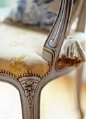 Pastellgelber Bezugsstoff mit erhabener Wappenlilie an antikem, geschnitztem Stuhlgestell