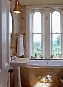 Kleines Bad im Antikstil mit Säulenwaschbecken und unter Fenster eingebaute Badewanne