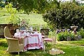 Gedeckter Tisch für den Nachmittagstee mit verschiedenen, alten Stühlen in romantischem Garten