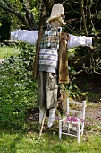 Im englischen Country-Stil gekleidete Vogelscheuche und weisser Kinderstuhl im Garten