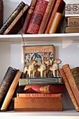 Alte Bücher mit Golddruck und Hundefiguren aus Porzellan in einem Regal