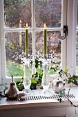 Brennende Kerzen in Glasleuchtern, versilberter Apfel und Birne zwischen Efeuranken auf einem Fensterbrett